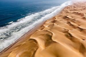 Langewand, Aerial view of where the Atlantic Ocean meets the sea of dunes in Western Namibia. by ClickAlps