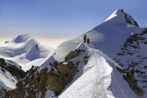 "Mountaineers climbing sharp ridge of ""crossing of Liskamm"", (traversata by ClickAlps"