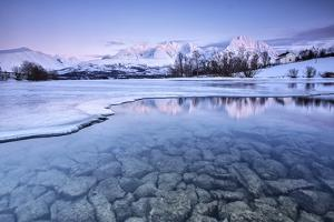 Snowy peaks are reflected in the frozen Lake Jaegervatnet at sunset Stortind Lyngen Alps Tromsa? La by ClickAlps