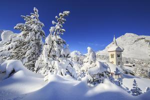 The bell tower submerged by snow surrounded by woods Maloja Canton of Engadine Switzerland Europe by ClickAlps