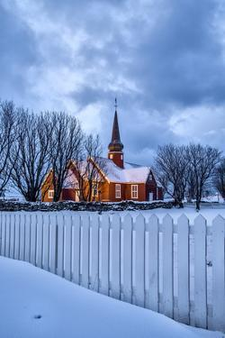 The illuminated church at dusk in the cold snowy landscape at Flakstad Lofoten Norway Europe by ClickAlps