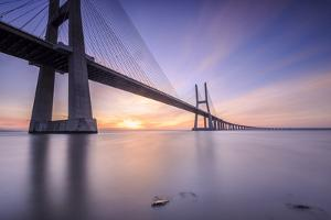 The sun rises on the Vasco da Gama Bridge that spans the Tagus River Lisbon Portugal Europe by ClickAlps