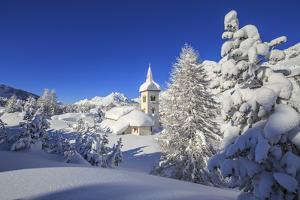 The winter sun illuminate the snowy landscape and the typical church Maloja Canton of Engadine Swit by ClickAlps