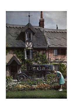A Woman Tends Her Garden Outside Her Cottage in Horning-On-The-Bure by Clifton R. Adams