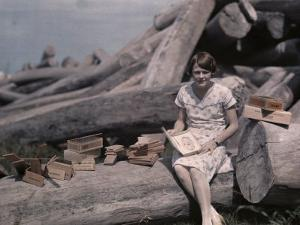 Girl Sits on a Log Among Cigar Boxes Crafted from Cedar Trees by Clifton R. Adams