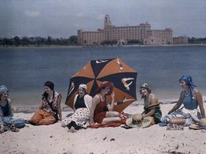Six Women Sit on a St. Petersburg Beach with the Water Behind Them by Clifton R. Adams