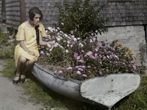Woman Sits on a Boat Now Serving as a Flower Bed by Clifton R. Adams