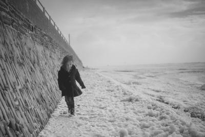 Young Girl Walking Beside the Sea Wall in England During Winter