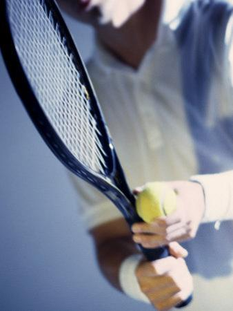 Close-up of a Young Man Holding a Tennis Racket and a Tennis Ball