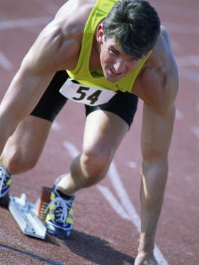 Close-up of a Young Man in the Starting Position on a Running Track