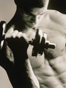 Close-up of a Young Man Working Out with a Dumbbell