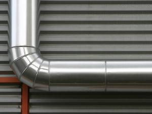 Close-Up of Industrial Pipe Against Metal Wall