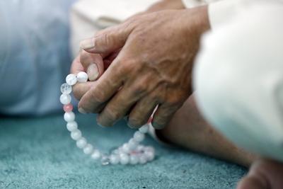 https://imgc.allpostersimages.com/img/posters/close-up-of-man-praying-in-a-mosque-with-tasbih-prayer-beads-masjid-al-rahim-mosque_u-L-Q1GYKRS0.jpg?artPerspective=n