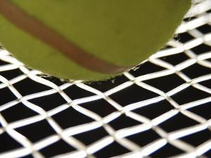 Close-Up of Tennis Ball on Webbing of Tennis Racket