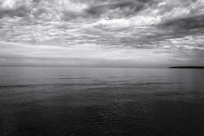 https://imgc.allpostersimages.com/img/posters/cloudscape-over-sea-distant-landmass-b-w_u-L-Q1CQQ2E0.jpg?artPerspective=n