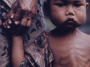 Close-Up of an Indonesian Child Holding on to the Hand of His Mother by Co Rentmeester