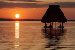 People Relaxing at Sunset, Lago Peten Itza, El Remate, Guatemala, Central America by Colin Brynn