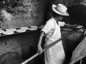 Communal Bakery in Primitive Mexican Village, Loaves of Bread Being Shoved into Adobe Oven
