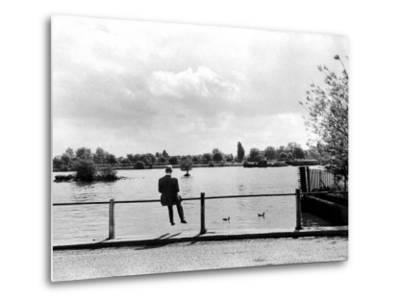 British Actor Alec Guinness Sitting Alone by Lake in a Park by Cornell Capa