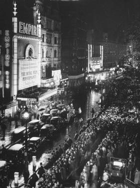 People Waiting in Front of the Brightly Lighted Empire Theatre for the Royal Film Performance by Cornell Capa