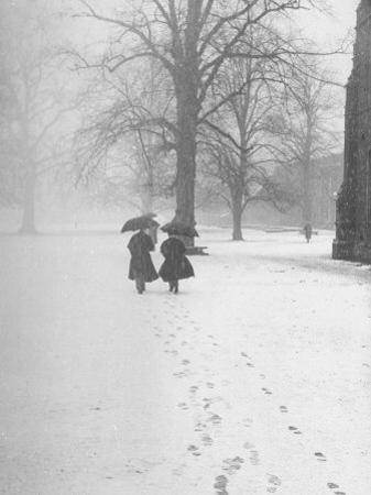 Snow Falling While People Take a Stroll Across Campus of Winchester College by Cornell Capa