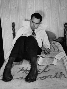 Vice Presidential Candidate Richard M. Nixon Sitting on His Hotel Bed Reviewing Paperwork by Cornell Capa