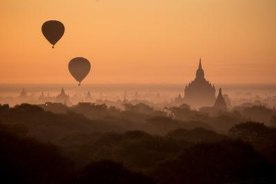 Hot Air Balloons Float Above the Terraces of a Buddhist Temple in Bagan by Cory Richards
