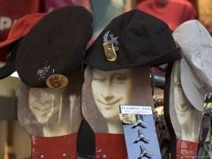 Display of Hats Perch on Cardboard Faces of the Mona Lisa by Cotton Coulson