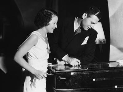 Couple Playing with Pinball Machine