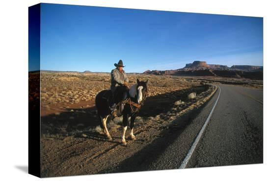Cowboy on his horse on a highway near Hanksville, Utah, USA--Stretched Canvas Print