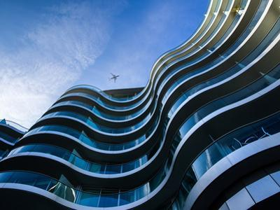 Modern Building with Aeroplane Above