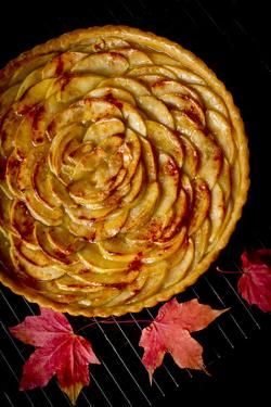 A Fresh Baked French Apple Tart with Colorful Fall Leaves Placed on a Cooling Rack by Cynthia Classen