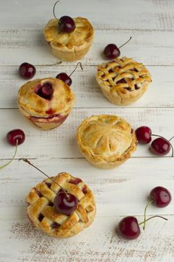 Five Freshly Baked Homemade Cherry Pies on a Rustic White Table Surrounded by a Few Fresh Cherries by Cynthia Classen