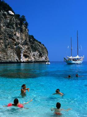 Tourists Swimming in Waters of Cala Mariolu in Gulf of Orosei, Sardinia, Italy by Dallas Stribley