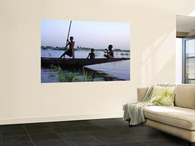 Three Boys Play on a Canoe (Pirogue) on the River in Mopti by Dan Herrick