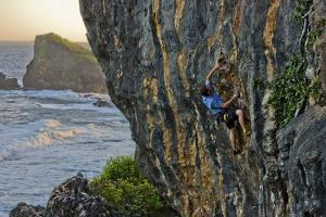 A Young Male Climber Ascends the Coastal Route: Kuda Laut a 5.11A in Siung Beach by Dan Holz
