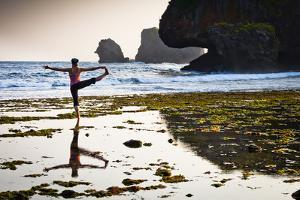 A Young Woman Practices Yoga at Low Tide During a Hazy Sunset at Siung Beach by Dan Holz