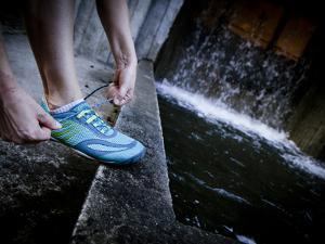 Lisa Eaton Laces Up Her Running Shoe Near a Water Feature at Freeway Park - Seattle, Washington by Dan Holz