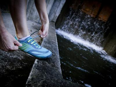 Lisa Eaton Laces Up Her Running Shoe Near a Water Feature at Freeway Park - Seattle, Washington