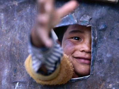 Boy Reaching through Hole in Gate, Alchi, Jammu and Kashmir, India