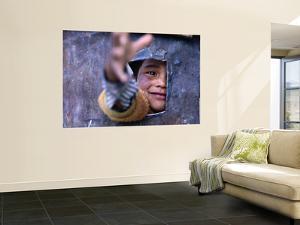 Boy Reaching through Hole in Gate, Alchi, Jammu and Kashmir, India by Daniel Boag