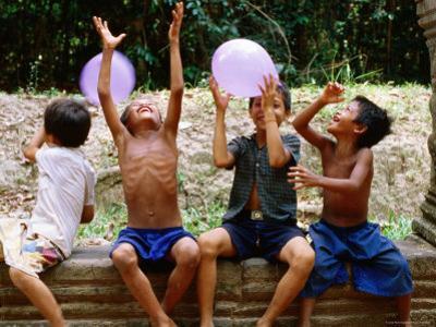 Local Boys Toss Balloons Outside Preah Kahn Temple, Siem Reap, Cambodia