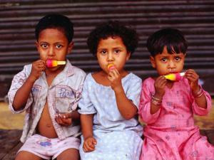 Three Children Eating Icy-Poles, Bengali Basti, Delhi, India by Daniel Boag