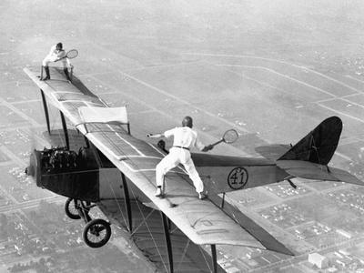https://imgc.allpostersimages.com/img/posters/daredevils-playing-tennis-on-a-biplane_u-L-PZS3VM0.jpg?p=0