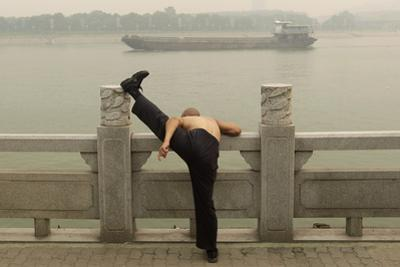 A Man Stretches His Leg on the Bank of the Han River as a Ship Passes by Amid Thick Haze in Wuhan