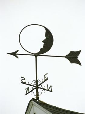 A Man-In-The-Moon Weather Vane on a Roof Top by Darlyne A. Murawski