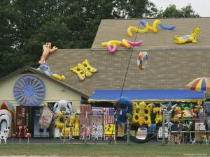 Inflatable Rafts and Beach Toys in Front of a Variety Store by Darlyne A. Murawski