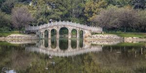 Chinese Bridge over Green Lake in Kunming, China by Darrell Gulin