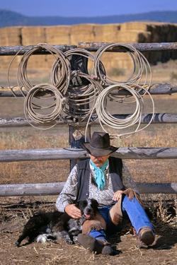 Cowboy and Dog Sitting Against Fence by Darrell Gulin