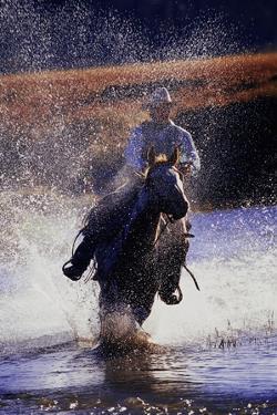 Cowboy Riding Horse Through River by Darrell Gulin